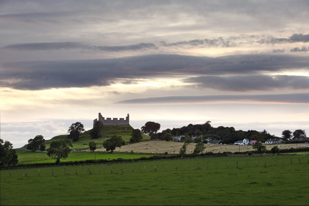 Hume castle viewed from a distance across some fields.